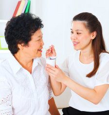 caregiver giving daily vitamin to senior woman