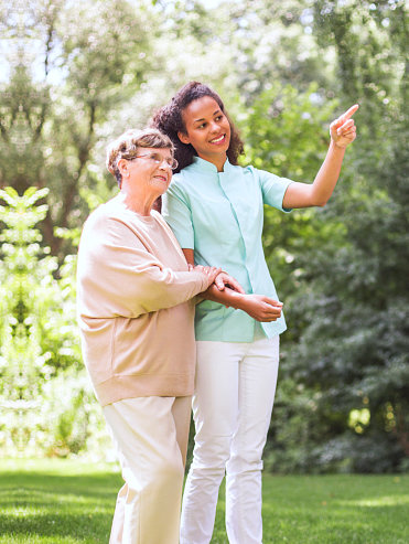 caregiver and senior woman walking in the park