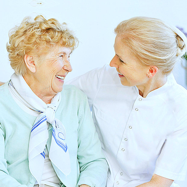 caregiver and senior woman smiling together