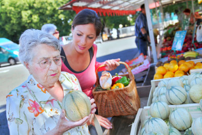 caregiver doing grocery shopping with senior woman