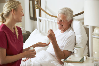 caregiver giving medication to senior man