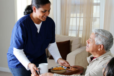 caregiver serving food to senior man